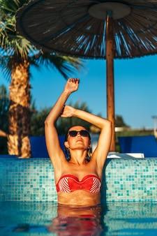 Jolie fille brune se détendre à la piscine