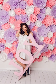 Jolie fille brune se dresse et tient le mot en bois joy souriant largement. elle a un fond rose en fleurs. elle joue avec les cheveux