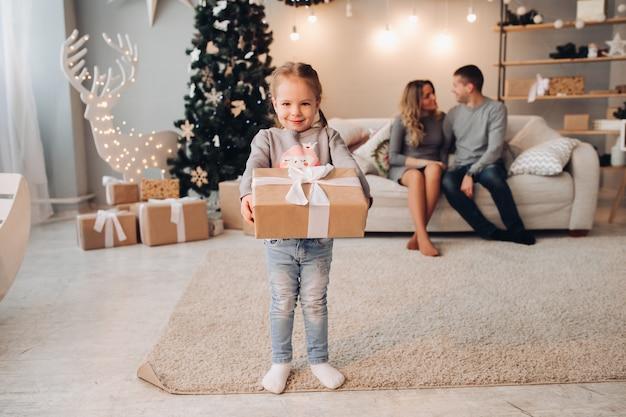 Jolie fille avec un cadeau contre ses parents.