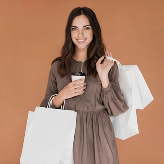 Jolie fille avec café et nombreux filets de magasins souriant à la caméra