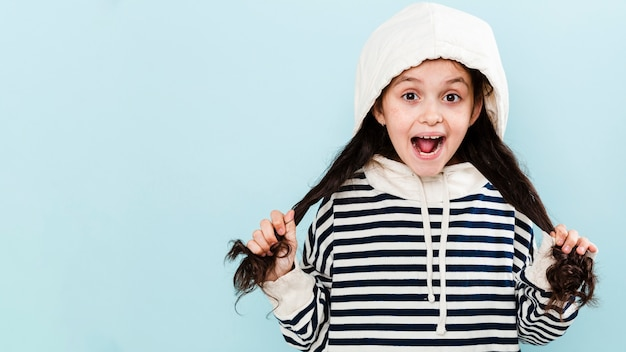 Jolie fille avec capuche jouant avec les cheveux