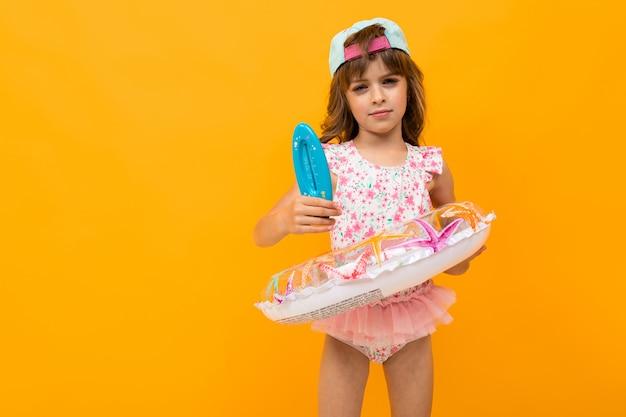 Jolie fille avec une casquette de baseball en maillot de bain avec un cercle de natation détient un thermomètre pour l'eau sur jaune
