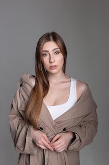 Jolie fille caucasienne aux cheveux longs et imperméable posant sur fond gris studio