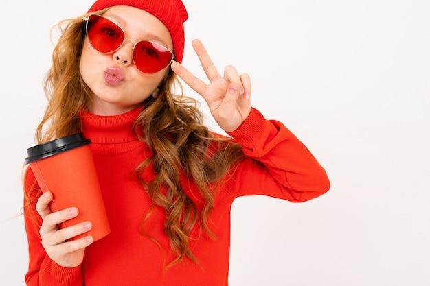 Jolie fille caucasienne charmante dans un chapeau d'hiver rouge et des lunettes de soleil est titulaire d'une tasse de café avec une maquette sur fond blanc