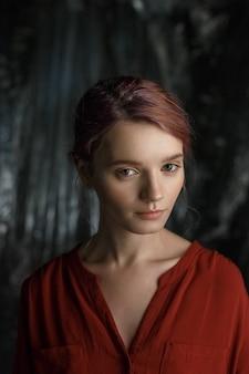 Jolie fille caucasienne en chemise rouge avec décolleté profond et clavicules ouverts debout sur fond de tissu flou
