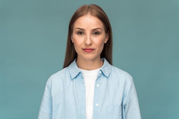 Jolie fille caucasienne portant un t-shirt blanc et une chemise en jean regardant directement dans la caméra. jeune femme posant sur un fond de mur bleu