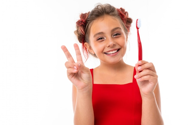 Jolie fille caucasienne en robe rouge détient brosse à dents et montre la paix isolé sur mur blanc