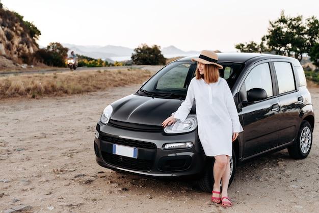 Jolie fille charmante dans un chapeau de paille pose autour d'une voiture noire sur le bord de la route.