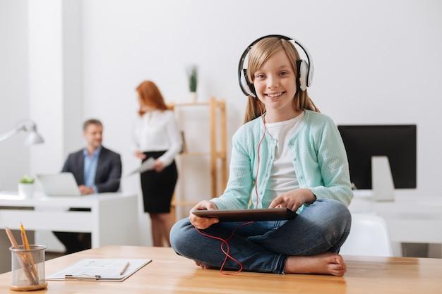 Jolie fille charmante intelligente assise sur la table et jouant avec son gadget pendant que son père travaille dur sur son projet