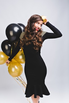 Jolie fille charmante avec de longs cheveux bruns bouclés célébrant son anniversaire sur blanc