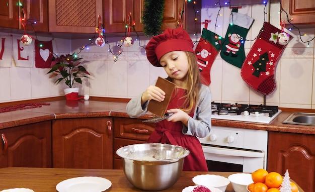 Une jolie fille chef frotte le chocolat sur une râpe dans un bol. sur la table sont orange, différents ingrédients pour la pâte. au fond de la cuisine se trouvent différentes décorations et guirlandes de noël