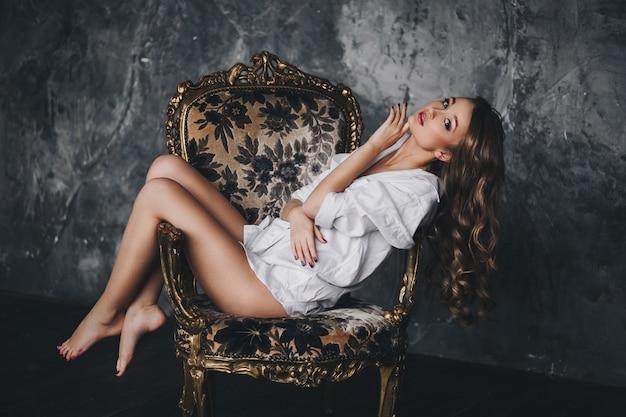 Jolie fille en chemise blanche assise sur une chaise vintage.
