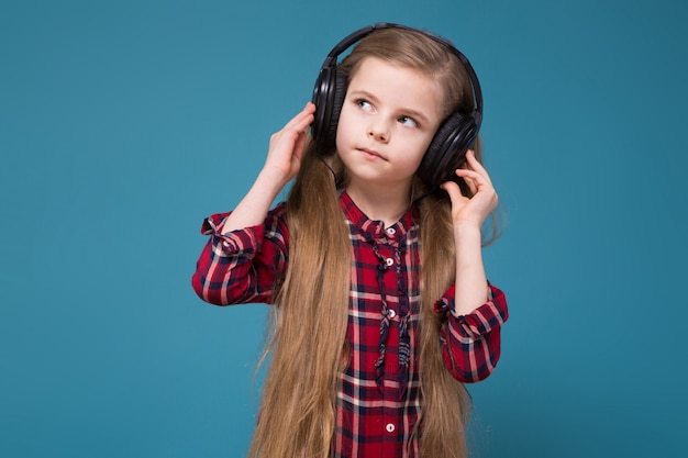 Jolie fille en chemise et écouteurs aux cheveux longs