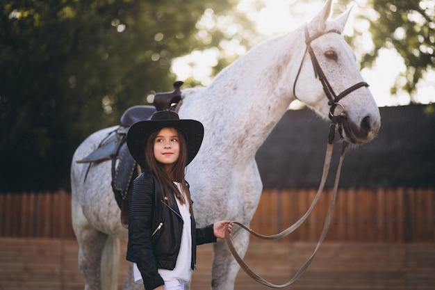 Jolie fille avec un cheval au ranch