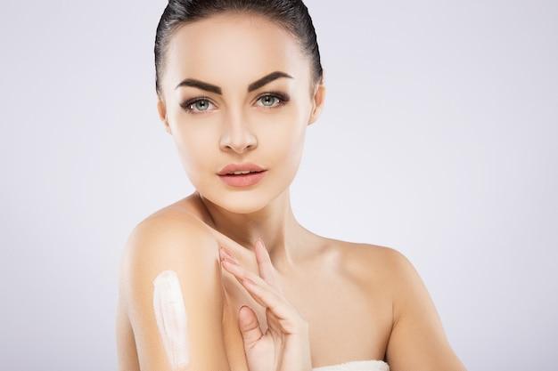 Jolie fille avec des cheveux noirs fixes derrière, de grands yeux foncés, une peau douce et des épaules nues à l'aide de crème, un modèle avec un maquillage nude clair, un portrait, une photo de beauté.