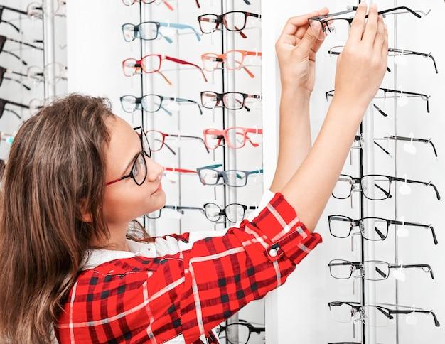 Jolie fille choisissant des lunettes optiques