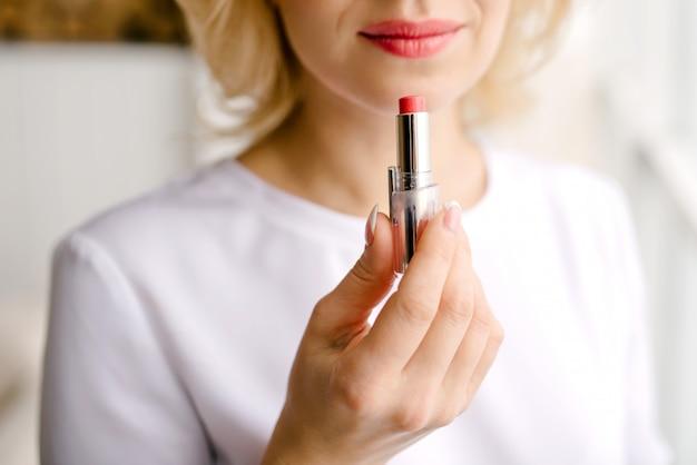 Jolie fille choisit le rouge à lèvres rouge