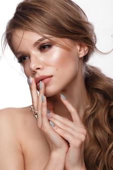 Jolie fille avec une coiffure facile, un maquillage classique, des lèvres nues et un dessin de manucure avec un pot de vernis à ongles dans ses mains,