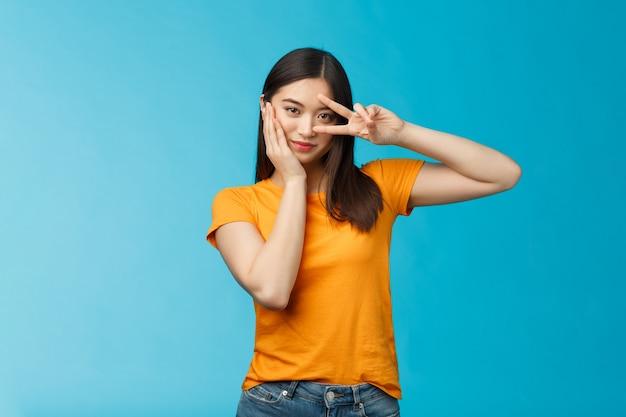 Une jolie fille coréenne asiatique élégante et affirmée montre un signe de victoire pour la paix sur les yeux, un regard tactile sur la joue habilité et motivé, debout sur fond bleu coquette et coquette, porte un t-shirt jaune