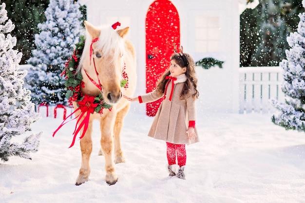 Jolie fille avec des cornes de cerf debout avec un cheval poney sous la neige.