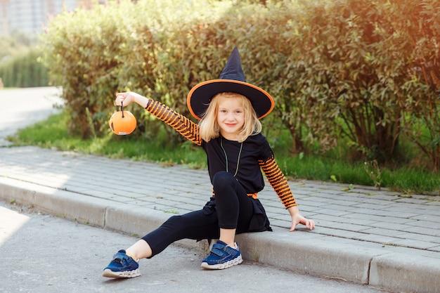 Jolie fille en costume d'halloween tenant jackolantern s'amusant trick or treat à l'extérieur en automne