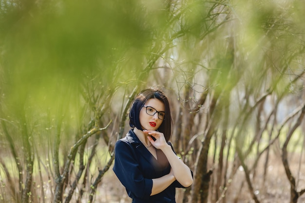 Jolie fille en costume noir parmi les buissons