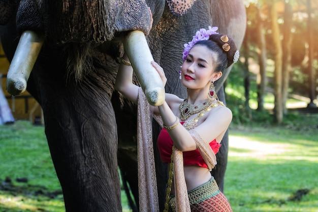 Jolie fille en costumes traditionnels thaïlandais touchant la trompe de l'éléphant