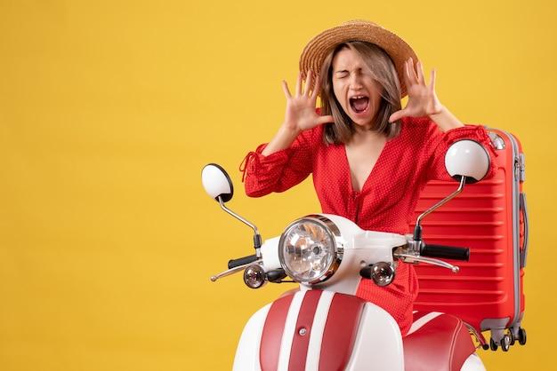 Jolie fille sur cyclomoteur avec valise rouge criant