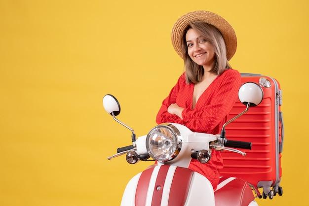 Jolie fille sur cyclomoteur avec valise rouge croisant les mains