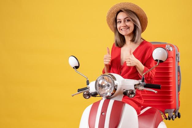 Jolie fille sur cyclomoteur avec valise rouge donnant le pouce vers le haut