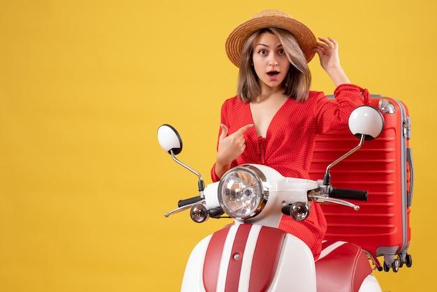 Jolie fille sur cyclomoteur avec valise rouge pointant sur elle-même