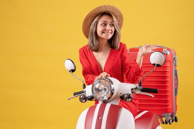 Jolie fille sur cyclomoteur avec valise rouge pointant vers la droite