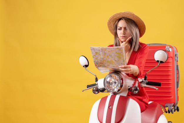 Jolie fille sur cyclomoteur avec valise rouge en regardant la carte