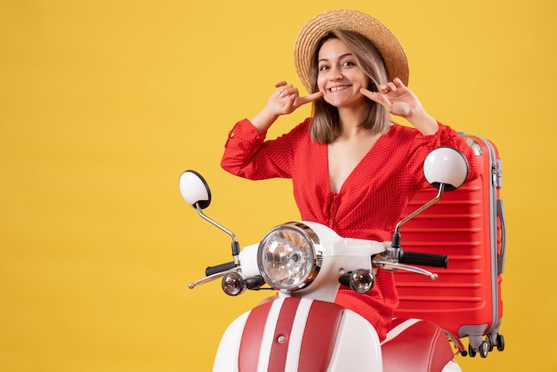 Jolie fille sur cyclomoteur avec valise rouge souriant