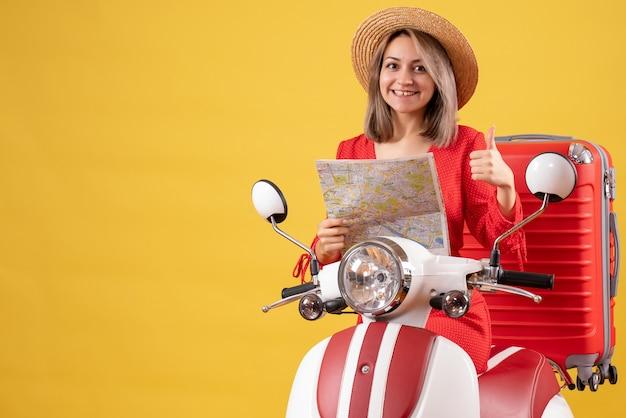 Jolie fille sur un cyclomoteur avec une valise rouge tenant une carte donnant des pouces vers le haut