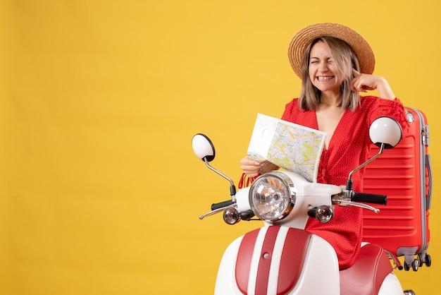 Jolie fille sur un cyclomoteur avec une valise rouge tenant une carte fermant son oreille