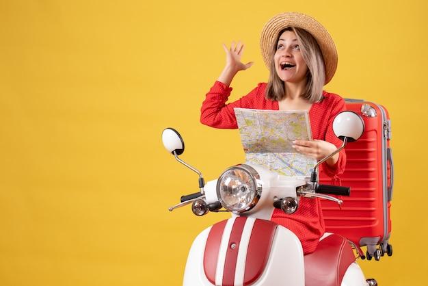 Jolie fille sur cyclomoteur avec valise rouge tenant la carte en levant