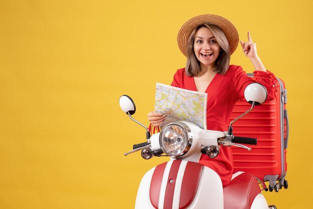 Jolie fille sur un cyclomoteur avec une valise rouge tenant une carte pointant le doigt vers le haut
