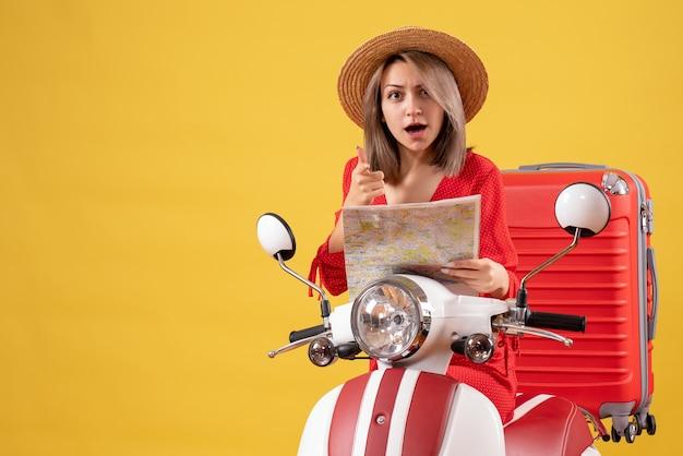 Jolie fille sur un cyclomoteur avec une valise rouge tenant une carte pointant vers la caméra