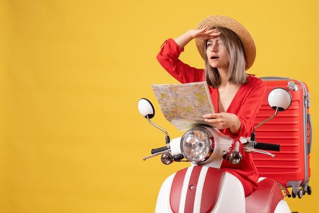 Jolie fille sur un cyclomoteur avec une valise rouge tenant une carte en regardant quelque chose
