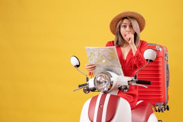 Jolie fille sur un cyclomoteur avec une valise rouge tenant une carte se demandant