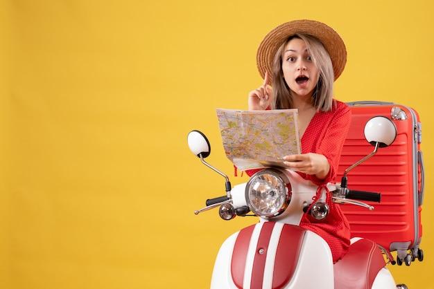 Jolie fille sur cyclomoteur avec valise rouge tenant une carte surprenante avec une idée