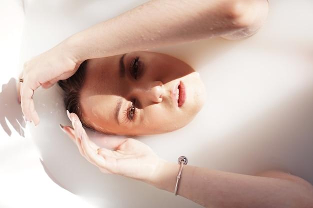 Jolie fille dans le bain avec du lait. soins de spa pour le rajeunissement de la peau. femme avec maquillage lumineux dans le salon spa. assez sexy relaxant dans le jacuzzi