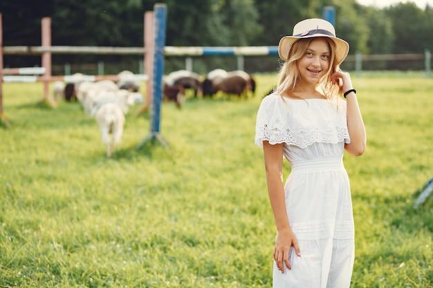 Jolie fille dans un champ avec une chèvre