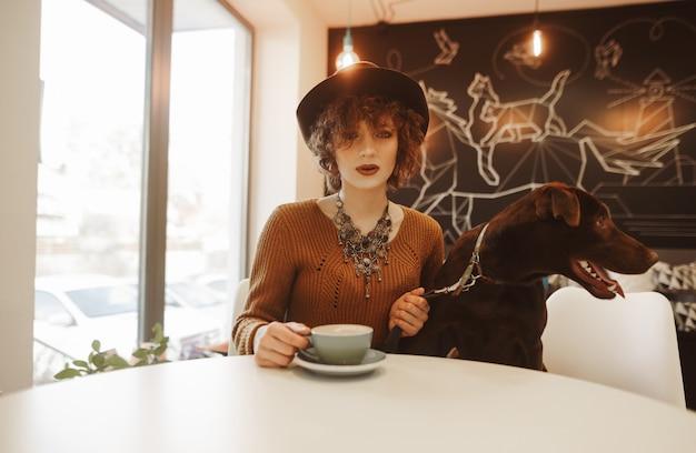 Jolie fille dans un chapeau et aux cheveux courts et bouclés se trouve dans un café confortable avec un chien