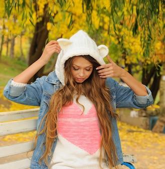 Jolie fille dans un chapeau d'ours tricoté posant dans le parc en automne.