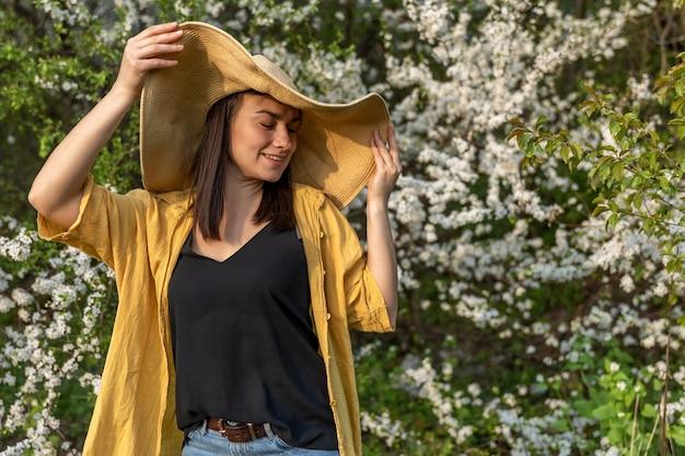 Une jolie fille dans un chapeau parmi les arbres en fleurs apprécie l'odeur des fleurs printanières