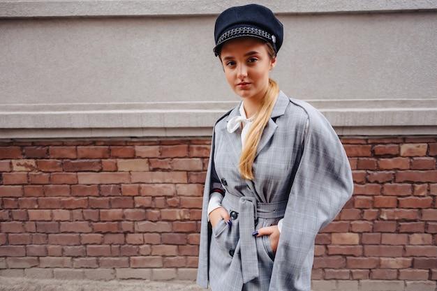 Une jolie fille dans un costume élégant se promène dans la ville et pose