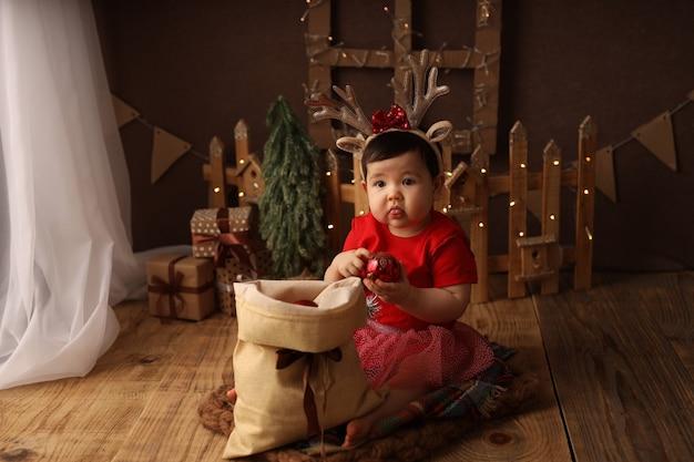 Une jolie fille dans un costume de noël rouge sort des jouets d'arbre de noël d'un sac avec des cadeaux