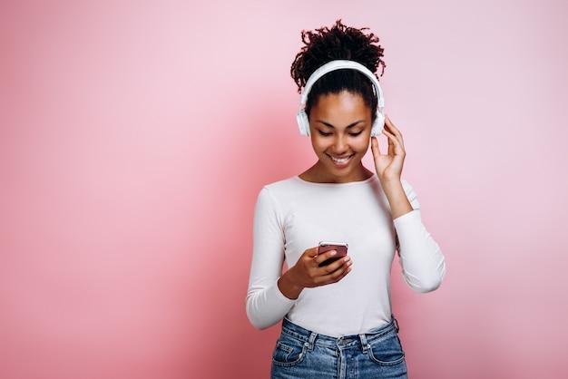 Jolie fille dans les écouteurs dans le studio allume la musique sur le téléphone